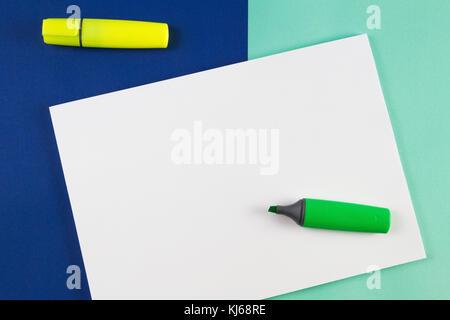 Gelb und grün Textmarker Marker mit leeren Blatt Papier auf blauem Hintergrund. - Stockfoto