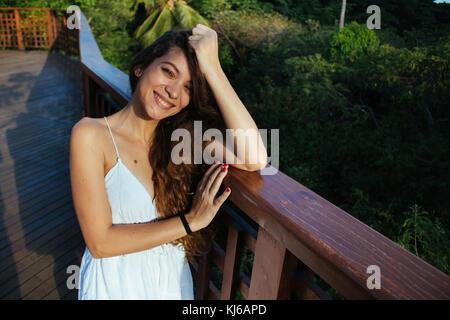 Junge Frau in weißem Kleid, auf dem im städtischen Park - Stockfoto