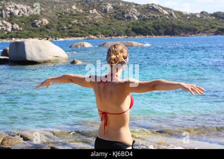 Eine junge erleichtert Frau hält die Hände als Ausdruck von Freiheit, von einer italienischen Strand am Meer. - Stockfoto
