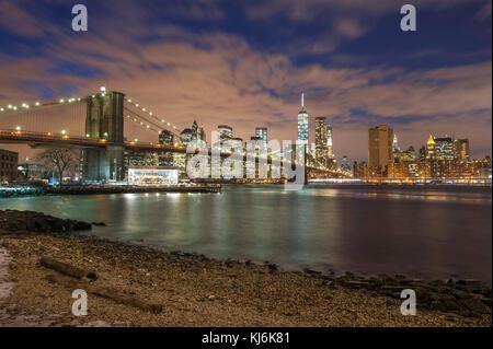 USA, New York City: Die Stadt bei Nacht und die Brooklyn Bridge leuchtet, East River, zwischen Brooklyn und Manhattan - Stockfoto