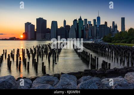 Wolkenkratzer von Manhattan und Holz-pilings bei Sonnenuntergang von Brooklyn Bridge Park. Manhattan, New York City