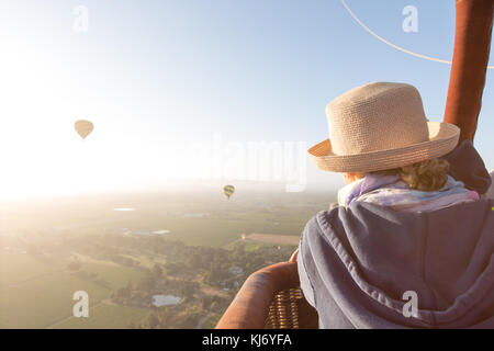 Eine Frau über den Korb eines Heißluftballons bei Sonnenaufgang in Napa Valley, Kalifornien - Stockfoto