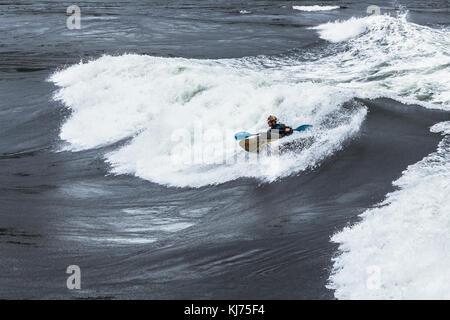 Eine behelmte Mann Kajaks das Gesicht von einer riesigen Welle in Sechelt Rapids, eines der schnellsten Gezeiten - Stockfoto