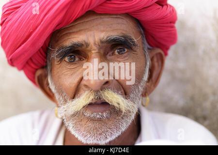 Porträt einer Rabari manwith Schnurrbärte in traditionelle weiße Kleidung und roten Turban in der Landschaft in - Stockfoto