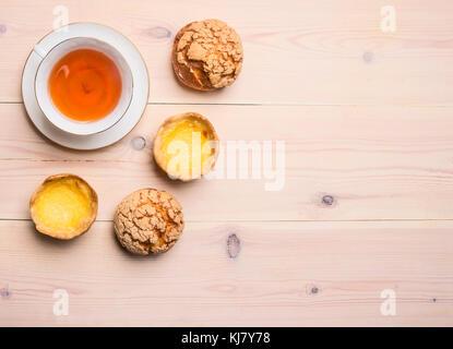 Frisch gebackene Brötchen mit Sahne und Zitrone liegen um eine Tasse Tee auf einem rustikalen Holzmöbeln Hintergrund - Stockfoto