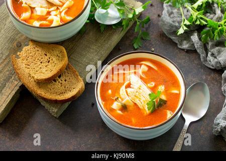 Tomatensuppe mit Nudeln und Hühnchen in einer Schüssel auf einem dunklen Stein Hintergrund. Das Konzept der gesunden - Stockfoto