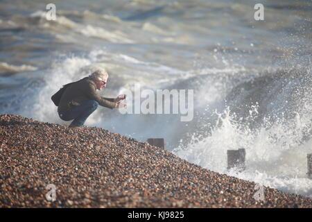 Hastings, East Sussex, UK. 22. November 2017. Ein Mann hockt auf dem Sand ein Bild von den rauen Bedingungen auf - Stockfoto