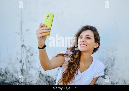 Junge schöne Frau, ihr Smartphone Holding, eine Selfie portrait nehmen - Stockfoto