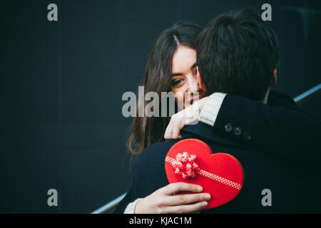 Schöne und glückliche junge Frau, die in der Liebe ihren Freund mit einem roten herzförmigen Geschenkbox umarmen - Stockfoto