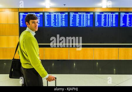Ein Geschäftsmann portrait vor der Anzeigetafel am Flughafen. - Stockfoto