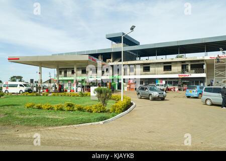 Eine Total Tankstelle mit im Bau befindlichen Gebäude dahinter und Kunden und Fahrzeuge auf dem Vorplatz, Kenia, - Stockfoto