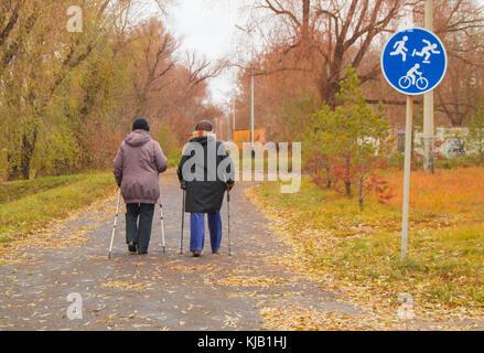 Nordic Walking für zwei ältere Frauen im Freien im Herbst Park. - Stockfoto