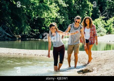 Lächelnd Freunde Waten im Fluss - Stockfoto