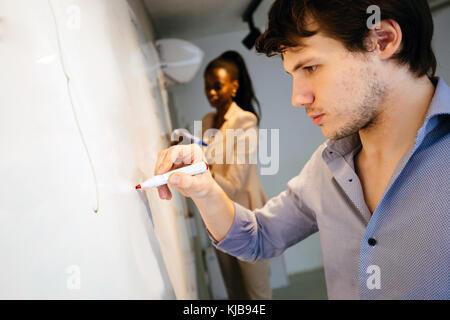 Intelligente Leute Schreiben auf dem Whiteboard - Stockfoto