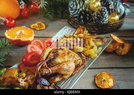 Wachtel mit Zitrone und Mandarine, gebraten mit roten Zwiebeln auf die Weihnachten Tabelle. Die horizontalen Rahmen. - Stockfoto