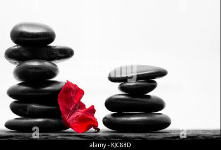 Zwei Türme von Gehefteten Kieselsteine auf einer Schiefertafel mit einer roten Rose petal - Stockfoto