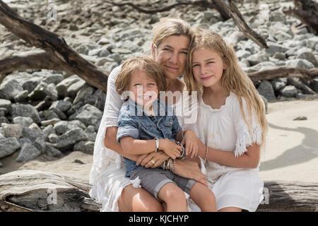 Kaukasische Familie sitzt auf Treibholz am Strand - Stockfoto