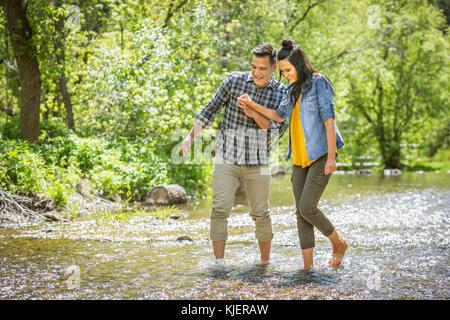Paar Hände halten das Waten im Fluss - Stockfoto