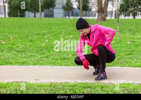 Junge Frau erschöpft nach Zug an einem kalten Wintertag auf der Spur eines städtischen Park. weiblichen Athleten - Stockfoto