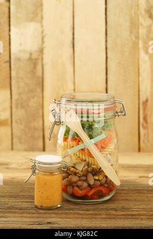 Veganer und vegetarischer Salat zum Mitnehmen im Glas mit roter Paprika, Nudeln, Bohnen, Walnüssen, Tofu, spiralisierten - Stockfoto
