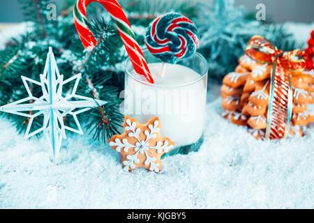 Weihnachten Lebkuchen und Milch mit Dekorationen, Schnee, Weihnachtsbaum Filialen auf das neue Jahr Hintergrund. - Stockfoto