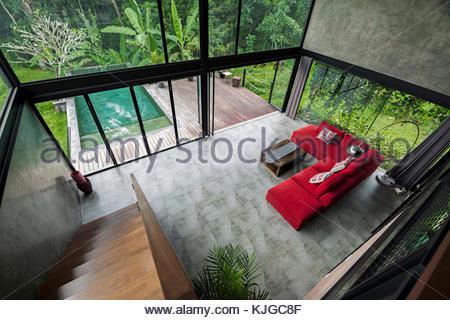 ... Modernes, Minimalistisches Wohnzimmer Mit Roten Couch In  Zeitgenössischem Design Haus Mit Glasfassade, Umgeben Von