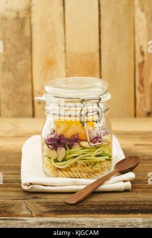 Veganer und vegetarischer Salat zum Mitnehmen im Glas mit Nudeln, spiralisierten Zucchini, Mandeln, Rotkohl und - Stockfoto