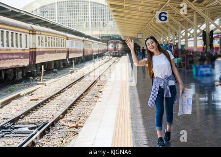 Asien Frau Gefühl, Glück und Gruß ihr Freund, bevor Sie am Bahnhof, Reisen und Lifestyle Konzept zu reisen - Stockfoto