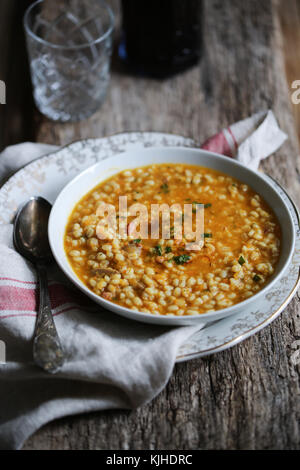 Kürbis, Pilze und Gerste Suppe in einer weißen Schüssel auf einen hölzernen Tisch. - Stockfoto