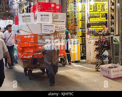 """Teheran, Iran - 22. Mai, 2107: Der Mensch zieht Wagen mit """"Jobticket"""" in Teheran Grand Bazaar überlastet. Der große - Stockfoto"""