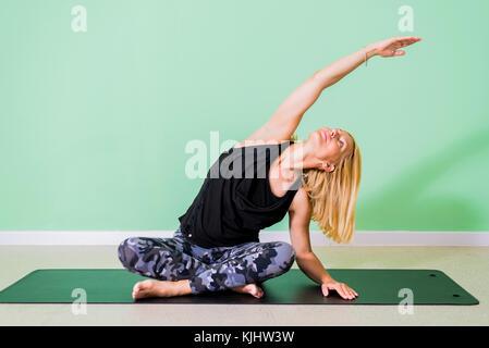 Frau Yoga im Studio auf dem Boden - Stockfoto