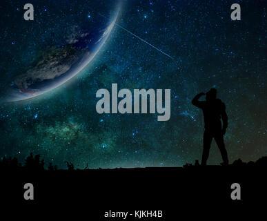 Die Silhouette eines Mannes, der stehen und auf die Erde mit milchstrasse Hintergrund, Elemente dieses Bild von - Stockfoto