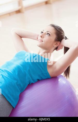 Attraktive junge Frau, die die Arbeit mit Fitness Ball in der Gym, Pilates Übung. - Stockfoto
