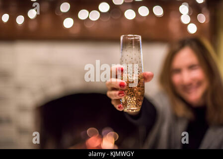 Frau mit Glas Champagner vor Kamin an Silvester - Stockfoto