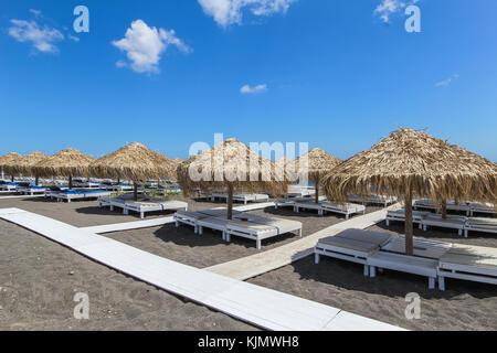 Reihe der liegestühle und der Sonnenschirme am schwarzen Sandstrand, Insel Santorini, Griechenland - Stockfoto
