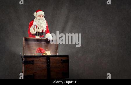 Santa Claus mit einem Geschenk auf einem Copyspace Hintergrund. - Stockfoto