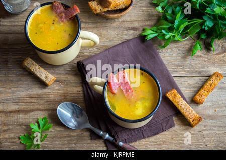 Split Erbsensuppe mit geräuchertem Schinken und Croutons auf Holzuntergrund. Gesunde hausgemachte Dicke split Suppe - Stockfoto