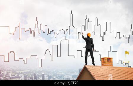 Mann Architekten zeichnen Silhouette der modernen Stadt am blauen Himmel. mixed Media - Stockfoto