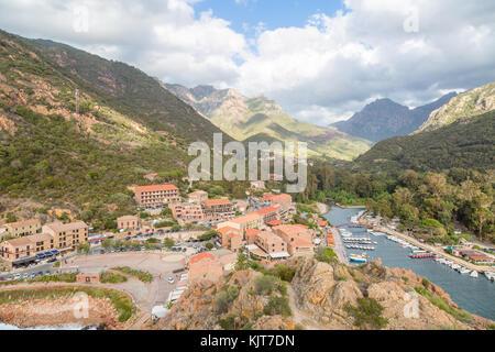 Stadt und den Hafen vor der Berge in der Bucht von Porto in Ota, Korsika, Frankreich - Stockfoto