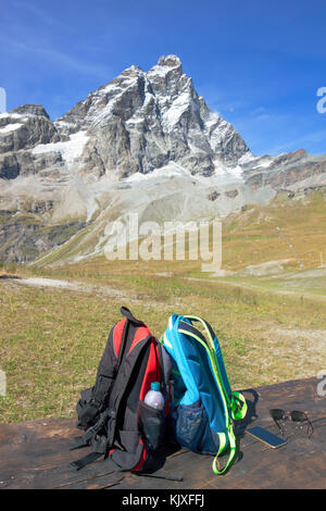Reisen zwei Rucksack auf der Holzbank mit Querformat mit Berg im Sommer Hintergrund. - Stockfoto