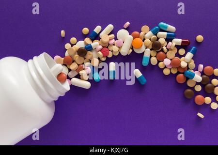 Gruppe von verschiedenen bunten Tabletten. Kapseln verschütten aus weiße Flasche. lila Hintergrund.line, weg Kurs - Stockfoto
