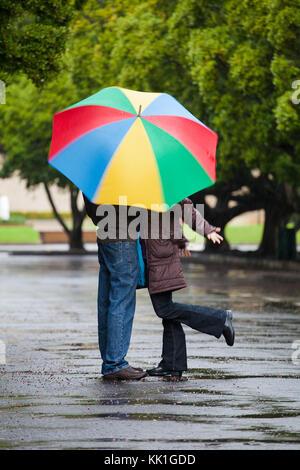 In der Nähe Bild von ein paar in der Liebe steht unter einem Sonnenschirm im Regen