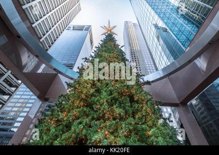 Hoch geschmückten Weihnachtsbaum überschattet von hohen downtown Wolkenkratzer, Houston, Texas - Unternehmen feiern - Stockfoto