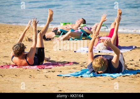 Las Palmas, Gran Canaria, Kanarische Inseln, Spanien. Touristen sonnenbaden, da lokale Rentner durch ihre Routine - Stockfoto