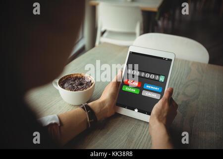 Mobile Display mit Memory Cleaner gegen Frau mit digitalen Tablet während Kaffee - Stockfoto