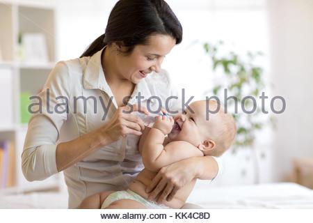 Mutter und Baby Wasser aus der Flasche sitzen auf dem Bett - Stockfoto