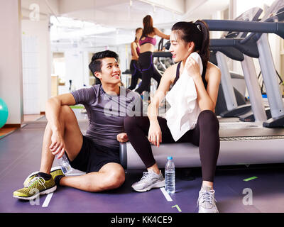 Jungen asiatischen Mann und Frau Chatten in der Turnhalle während der Einnahme eine Pause. - Stockfoto