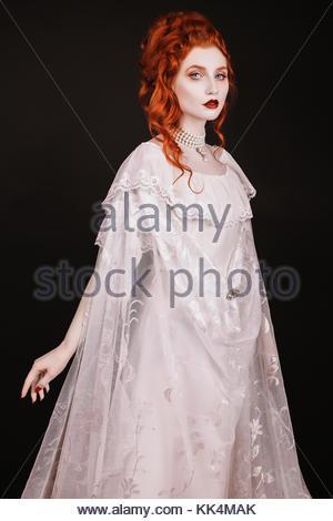 Rothaarige Frau in weißem Kleid mit blasser Haut auf schwarzem Hintergrund. Frau Vampir im gotischen Stil im Halloween - Stockfoto