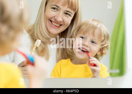Mutter lehrt Kinder Zähne putzen - Stockfoto