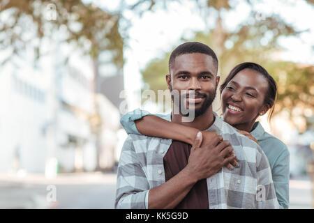 Lächelnden jungen afrikanischen Paar außerhalb an einem sonnigen Tag - Stockfoto